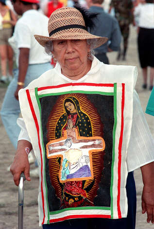 A worshiper wears an apron with the Virgen de Guadalupe during her visit to Westover Hills where Pope John Paul II celebrated Mass Sunday, Sept. 13, 1987 during his visit to San Antonio. Photo: San Antonio Express-News File Photo / SAN ANTONIO EXPRESS-NEWS
