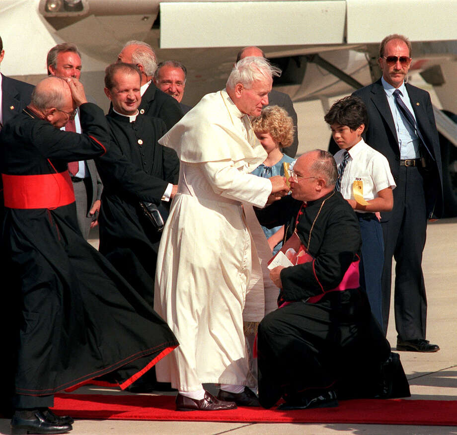 Archbishop Patrick Flores kneels down and kisses Pope John Paul's II hand as he gets off the airplane at Kelly AFB, in San Antonio, in September 1987. Photo: San Antonio Express-News File Photo / SAN ANTONIO EXPRESS-NEWS