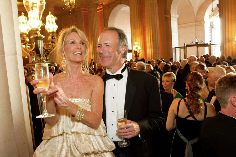 For the San Francisco Opera opening night in 2008, Belinda Berry wore a tiered dress using fabric from her bedskirt. She and her date, Tom Barrett, are seen appreciating musicians playing during the cocktail hour at the War Memorial Opera House in San Francisco. Photo: Laura Morton / Special To The Chronicle / ONLINE_YES