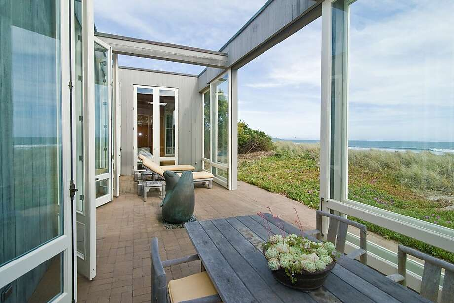 A porch with glass walls and brick floors faces the Pacific Ocean, with sea grasses bending towards the terrace to touch the simple exterior design. Photo: Photography By Rob Vente