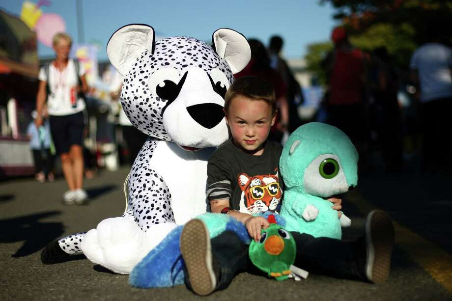 Kaiden Dhao, 4, sits with prizes he won popping balloons with darts during the opening day of the Puyallup Fair on Friday, September 7, 2012. The fair, one of the largest in the county, runs until September 23rd. Photo: JOSHUA TRUJILLO / SEATTLEPI.COM