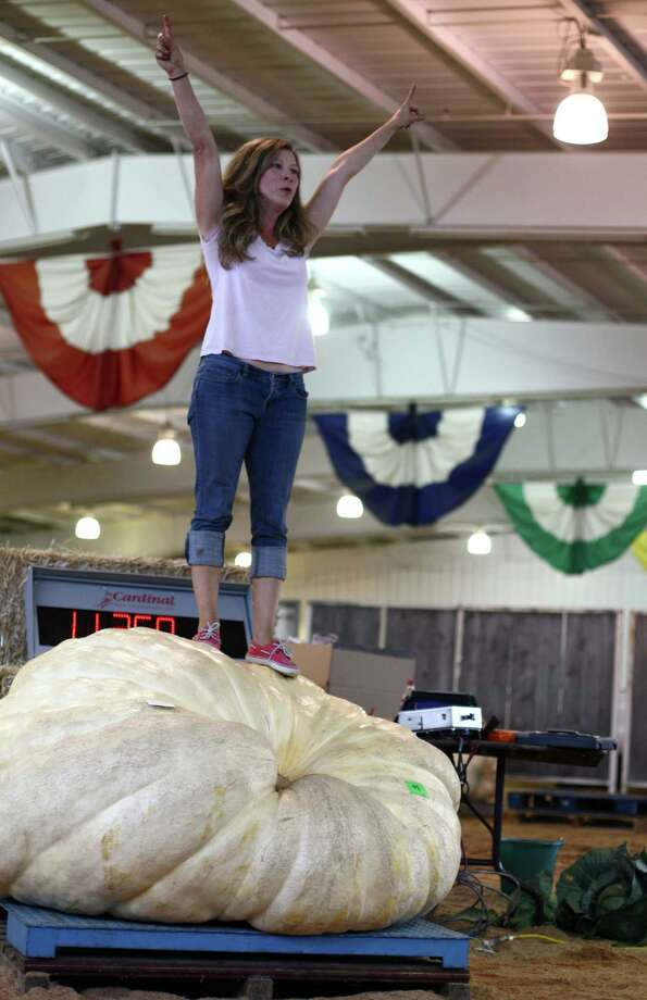 Cindy Tobeck stands atop her 1,135 pound giant pumpkin as it she competes in the giant pumpkin competition during the opening day of the Puyallup Fair on Friday, September 7, 2012. The fair, one of the largest in the county, runs until September 23rd. Photo: JOSHUA TRUJILLO / SEATTLEPI.COM