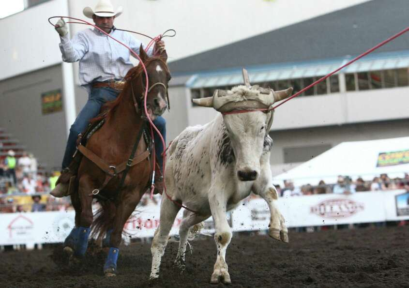 Cowboys participate in team calf roping during the Puyallup Pro Rodeo on the opening day of the Puya