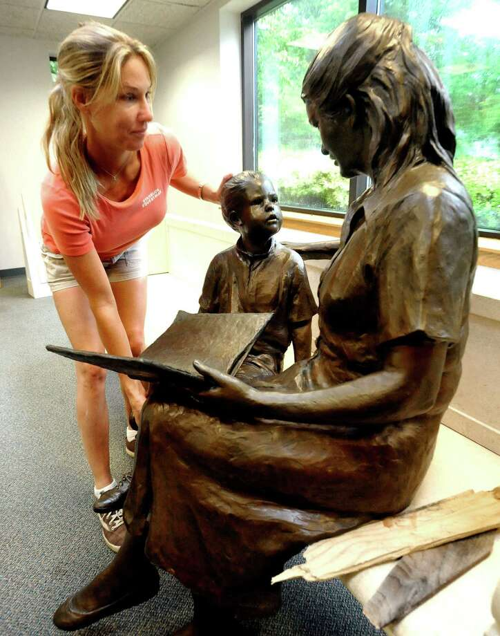 """Juliana Starbuck, a volunteer at the Ridgefield Public Library, moves """"Storytime,"""" a statue, during the library's tag sale Saturday, Sept. 9, 2012. Photo: Michael Duffy / The News-Times"""