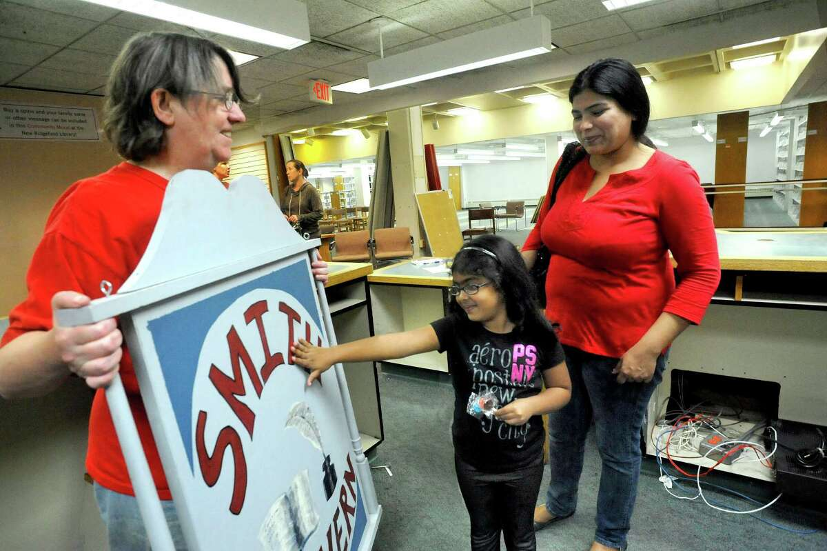 Mary Rindfleisch, assistant director at the Ridgefield Public Library, left, shows a Smith Tavern sign to Vanshika Ravula, 5, and Pragati Reddy, during the library's tag sale Saturday, Sept. 9, 2012. Smith Tavern was a stagecoach inn at the site the library now occupies.