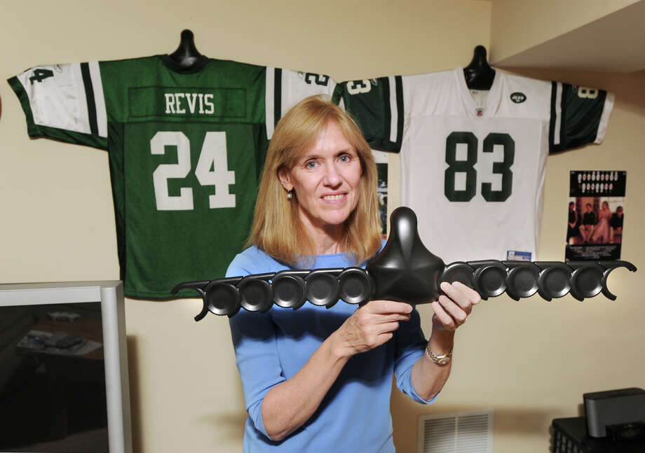 Pat Calanca, the president of ShirtWhiz, holds a ShirtWhiz, an affordable wall hanger for jerseys and shirts, that she uses to display New York Jets football jerseys in the basement of her New Canaan home, Thursday, Aug. 30, 2012. Photo: Bob Luckey / Greenwich Time