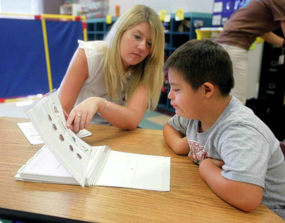 Rafael Hidalgo, 6, prepares to take a reading assessment test from researcher Kelly Burgoyne at Stone Oak Elementary. Photo: William Luther, San Antonio Express-News / © 2012 San Antonio Express-News