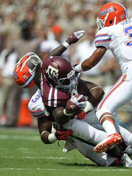 University of Florida linebacker Jelani Jenkins (3) helmet flies off as he tackles Texas A&M University running back Christine Michael (33) during the first quarter. Photo: Nick De La Torre, Houston Chronicle / © 2012  Houston Chronicle