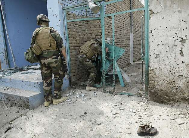 French soldiers from the NATO forces inspect the scene of a suicide attack in Kabul, Afghanistan, Saturday, Sept. 8, 2012. A suicide bomber blew himself up near NATO headquarters in the Afghan capital on Saturday, killing at least six people, police said. (AP Photo/Musadeq Sadeq) Photo: Musadeq Sadeq, Associated Press