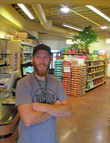 In this photo made Monday Aug. 27, 2012,  Boise Co-op pet food buyer Zach Jones poses in Boise, Idaho in the store's new space dedicated to natural pet food and supplies. Opening up a separate storefront for the fast-growing pet food segment is one of the ways the 39-year-old co-op is gearing up for increased competition from Whole Foods Market, which opens in Boise in October. (AP Photo/John Miller) Photo: John Miller