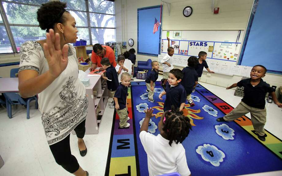 Pre-K teacher Chaka Burroughs, left, leads students in a dance to line up to go outside, at the Caroll Early Childhood Center in SAISD.  Thursday, August 30, 2012. Photo: BOB OWEN, San Antonio Express-News / San Antonio Express-News