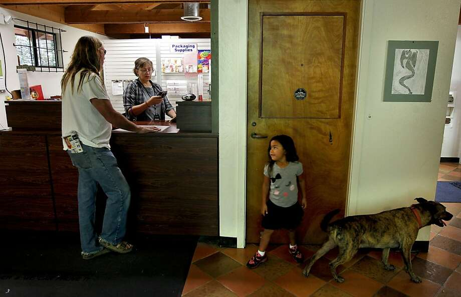 Eliana Murdock, 4-years-old watches over Scrappy as her grandfather Rocky Murdock conducts Post Office business with Carla Williams, a Postmaster Relief employee, on Thursday August 30, 2012, in Canyon, Calif. The town of Canyon is fighting to save it's Post Office from closure, which doubles as a community center. It's the latest Bay Area city to take on the United States Postal Service. Photo: Michael Macor, The Chronicle