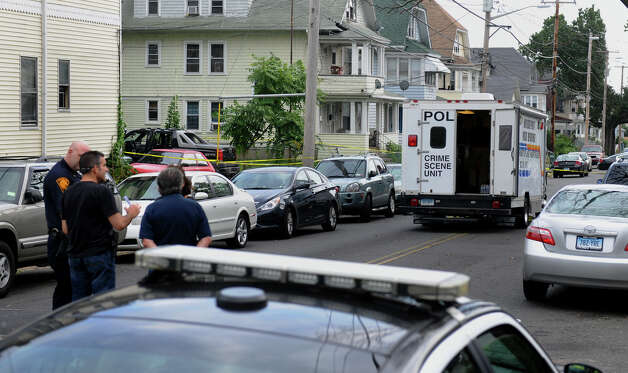 Bridgeport police investigate at the scene of a shooting along Bishop Street in Bridgeport, Conn. on Saturday September 8, 2012. The truck involved in the shooting can be seen above the officers surrounded by crime scene tape. Photo: Christian Abraham / Connecticut Post