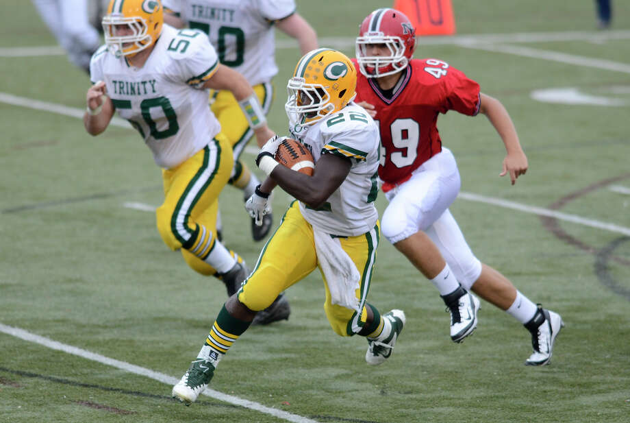 Trinity's #22 Shaquan Howsie earns some yardage ahead of New Canaan's Kevin Mcdonough as New Canaan High School hosts Trinity Catholic High School in varsity football in New Canaan, CT on Saturday September 24, 2011. Photo: Shelley Cryan / Shelley Cryan freelance; Stamford Advocate freelance
