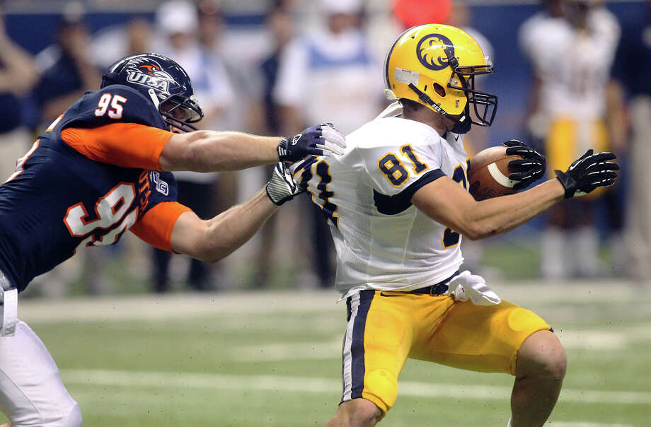 UTSA's Dan Winter (95) grabs onto Texas A&M-Commerce's Nathan James (81) at the Alamodome on Saturday, Sept. 8, 2012. The Roadrunners defeated the Lions, 27-16. Over 30,000 were in attendance. Photo: Kin Man Hui, Express-News / ©2012 San Antonio Express-News