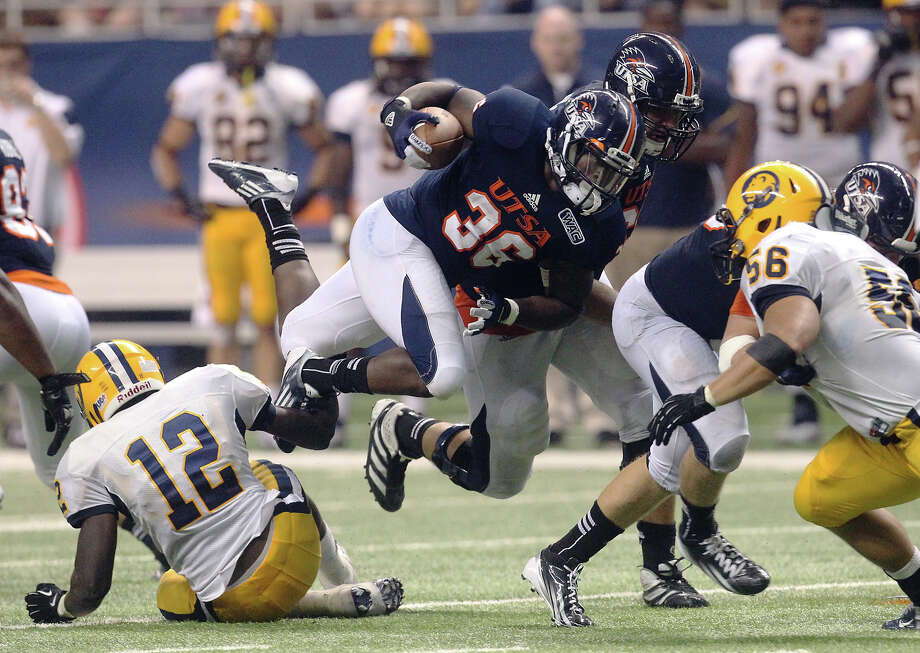UTSA's Evan Okotcha (36) gets off his feet during a run against Texas A&M-Commerce's Joel Wren (12) and Matt Claggett (56) in the first half at the Alamodome on Saturday, Sept. 8, 2012. The Roadrunners defeated the Lions, 27-16. Over 30,000 were in attendance. Photo: Kin Man Hui, Express-News / ©2012 San Antonio Express-News