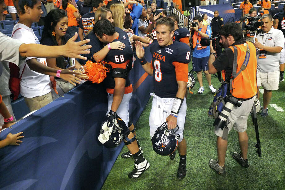 UTSA players including quarterback Eric Soza (08) high-five the crowd after their victory against Texas A&M-Commerce at the Alamodome on Saturday, Sept. 8, 2012. The Roadrunners defeated the Lions, 27-16. Over 30,000 were in attendance. Photo: Kin Man Hui, Express-News / ©2012 San Antonio Express-News