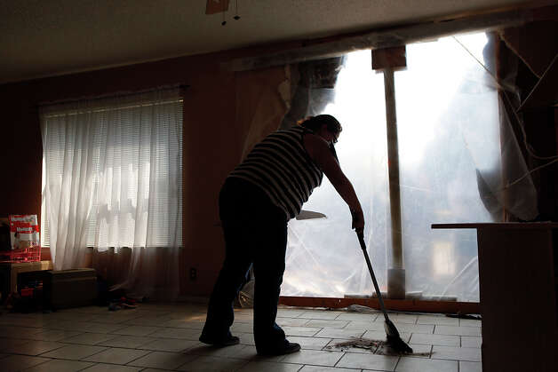 Peggy Ann Castillo cleans up debris in her home after a car drove into her house, making a large whole in the wall, right, a result of a two car accident at the intersection next to the house, in San Antonio on Saturday, Sept. 8, 2012. Photo: LISA KRANTZ, San Antonio Express-News / © 2012 San Antonio Express-News