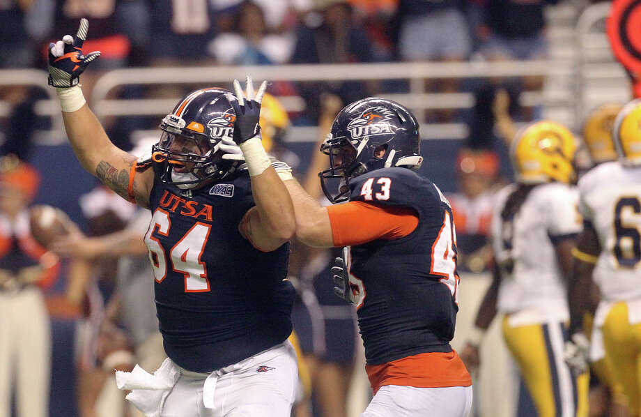 UTSA's Franky Anaya (64) reacts after intercepting a pass as teammate Cody Rogers congratulates Anaya on the play against Texas A&M-Commerce in the first half at the Alamodome on Saturday, Sept. 8, 2012. Photo: Kin Man Hui, Express-News / ©2012 San Antonio Express-News