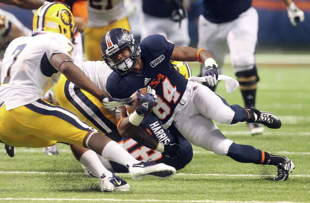 UTSA's Brandon Freeman leans in for yardage against Texas A&M-Commerce's Robert Wheeler (07) at the Alamodome on Saturday, Sept. 8, 2012. The Roadrunners defeated the Lions, 27-16. Over 30,000 were in attendance. Photo: Kin Man Hui, Express-News / ©2012 San Antonio Express-News