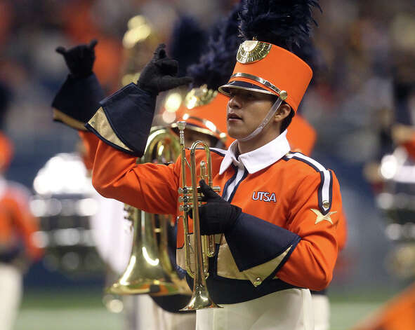 A UTSA marching band member flashes the roadrunner symbol as they take the field before the football game against Texas A&M-Commerce in the first half at the Alamodome on Saturday, Sept. 8, 2012. Photo: Kin Man Hui, Express-News / ©2012 San Antonio Express-News