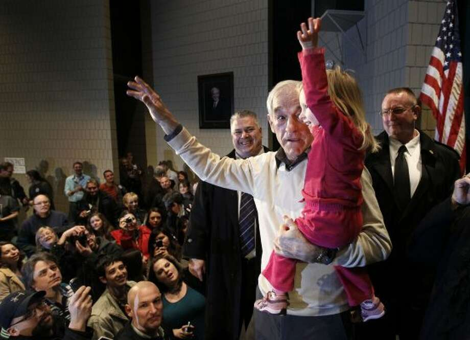 Republican presidential candidate Ron Paul shows 2-year-old Piper DeYoung how to wave to the crowd during a campaign stop Saturday, Feb. 4, 2012, in Rochester, Minn. (Charles Rex Arbogast / The Associated Press)
