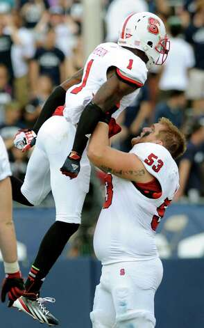 North Carolina State's David Amerson, left and Camden Wentz celebrate late in the second half of North Carolina's 10-7 victory over Connecticut in their NCAA college football game in East Hartford, Conn., on Saturday, Sept. 8, 2012. (AP Photo/Fred Beckham) Photo: Fred Beckham, Associated Press / FR153656 AP