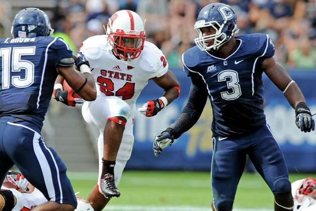 North Carolina State's James Washington, center, is pursued by Connecticut's Ty-Meer Brown, left, and Sio Moore late in the second half of their NCAA college football game in East Hartford, Conn., Saturday, Sept. 8, 2012. North Carolina State won 10-7. (AP Photo/Fred Beckham) Photo: Fred Beckham, Associated Press / FR153656 AP