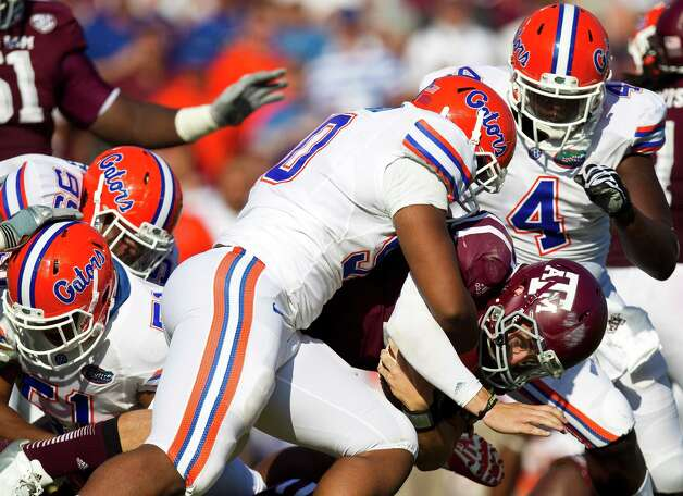 University of Florida defensive lineman Jonathan Bullard (90) tackles Texas A&M University quarterback Johnny Manziel (2) during the fourth quarter of a NCAA football game, Saturday, Sept. 8, 2012, at Kyle Field in College Station. The University of Florida won 20-17. Photo: Nick De La Torre, Houston Chronicle / © 2012  Houston Chronicle