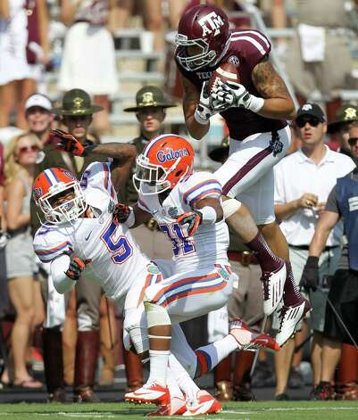 Texas A&M University wide receiver Mike Evans (13) is unable to land inbounds after making a catch over University of Florida defensive back Marcus Roberson (5) and University of Florida defensive back Cody Riggs (31) during the second quarter of a NCAA football game, Saturday, Sept. 8, 2012, at Kyle Field in College Station. Photo: Nick De La Torre, Houston Chronicle / © 2012  Houston Chronicle