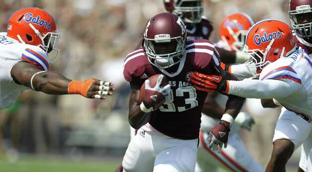 Texas A&M University running back Christine Michael (33) looks to power run past University of Florida defensive lineman Dominique Easley (2) and University of Florida linebacker Darrin Kitchens (49) during the first quarter of a NCAA football game, Saturday, Sept. 8, 2012, at Kyle Field in College Station. Photo: Nick De La Torre, Houston Chronicle / © 2012  Houston Chronicle