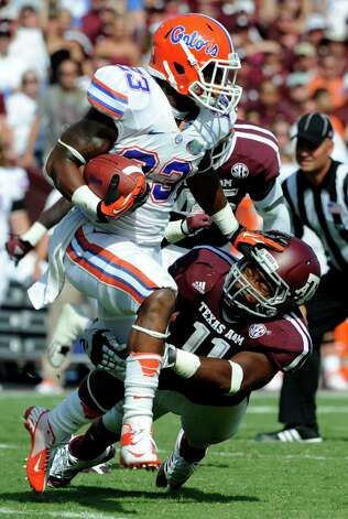 Florida running back Mike Gillislee (23) rushes for a gain as Texas A&M linebacker Jonathan Stewart (11) tries to tackle him during the third quarter of an NCAA college football game, Saturday, Sept. 8, 2012, in College Station, Texas. Florida beat Texas A&M 20-17. (AP Photo/Dave Einsel) Photo: Dave Einsel, Associated Press / FR43584 AP
