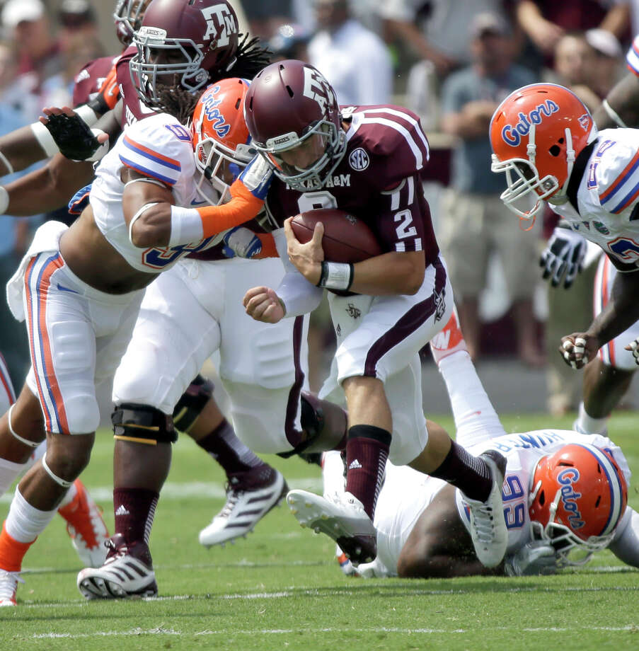Texas A&M quarterback Johnny Manziel (2) rushes for a first down as Florida defensive back Josh Evans (9) hits him during the first quarter of an NCAA college football game, Saturday, Sept. 8, 2012, in College Station, Texas. Texas A&M begins a new era with its first Southeastern Conference game after leaving the Big 12 Conference. (AP Photo/David J. Phillip) Photo: David J. Phillip, Associated Press / AP