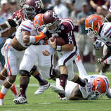Texas A&M quarterback Johnny Manziel (2) rushes for a first down as Florida defensive back Josh Evans (9) hits him during the first quarter of an NCAA college football game, Saturday, Sept. 8, 2012, in College Station, Texas. Texas A&M begins a new era with its first Southeastern Conference game after leaving the Big 12 Conference. (AP Photo/David J. Phillip)