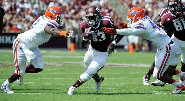 Texas A&M running back Christine Michael (33) rushes for a gain as Florida defensive lineman Dominique Easley, left, and linebacker Darrin Kitchens, right, defend during the second quarter of an NCAA college football game, Saturday, Sept. 8, 2012, in College Station, Texas. Texas A&M begins a new era with its first Southeastern Conference game after leaving the Big 12 Conference. (AP Photo/Dave Einsel) Photo: Dave Einsel, Associated Press / FR43584 AP