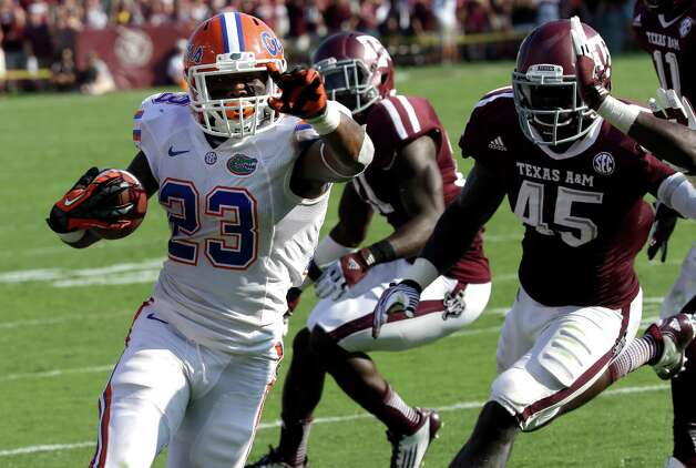 Florida running back Mike Gillislee (23) rushes for a touchdown as Texas A&M's Steven Jenkins (45) and Deshazor Everett, right, defend during the fourth quarter of an NCAA college football game, Saturday, Sept. 8, 2012, in College Station, Texas. Texas A&M begins a new era with its first Southeastern Conference game after leaving the Big 12 Conference. Florida beat Texas A&M 20-17. (AP Photo/David J. Phillip) Photo: David J. Phillip, Associated Press / AP