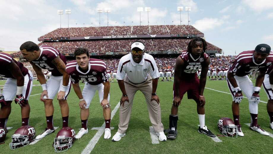 "Texas A&M coach Kevin Sumlin, center, sings the ""Aggie War Hymn"" with his players before an NCAA college football game against Florida, Saturday, Sept. 8, 2012, in College Station, Texas. Texas A&M begins a new era with its first Southeastern Conference game after leaving the Big 12 Conference. (AP Photo/David J. Phillip) Photo: David J. Phillip, Associated Press / AP"