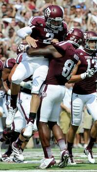 Texas A&M quarterback Johnny Manziel (2) is lifted by Nehemiah Hicks (81) after rushing for a touchdown against Florida during the second quarter of an NCAA college football game, Saturday, Sept. 8, 2012, in College Station, Texas. Texas A&M begins a new era with its first Southeastern Conference game after leaving the Big 12 Conference. (AP Photo/Dave Einsel) Photo: Dave Einsel, Associated Press / FR43584 AP