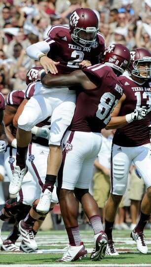 Texas A&M quarterback Johnny Manziel (2) is lifted by Nehemiah Hicks (81) after rushing for a touchd