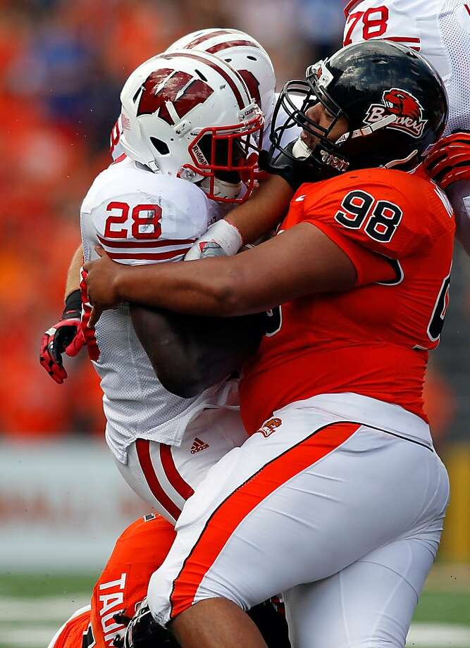 Castro Masaniai (98) helps Oregon State bottle up Montee Ball. Photo: Jonathan Ferrey, Getty Images
