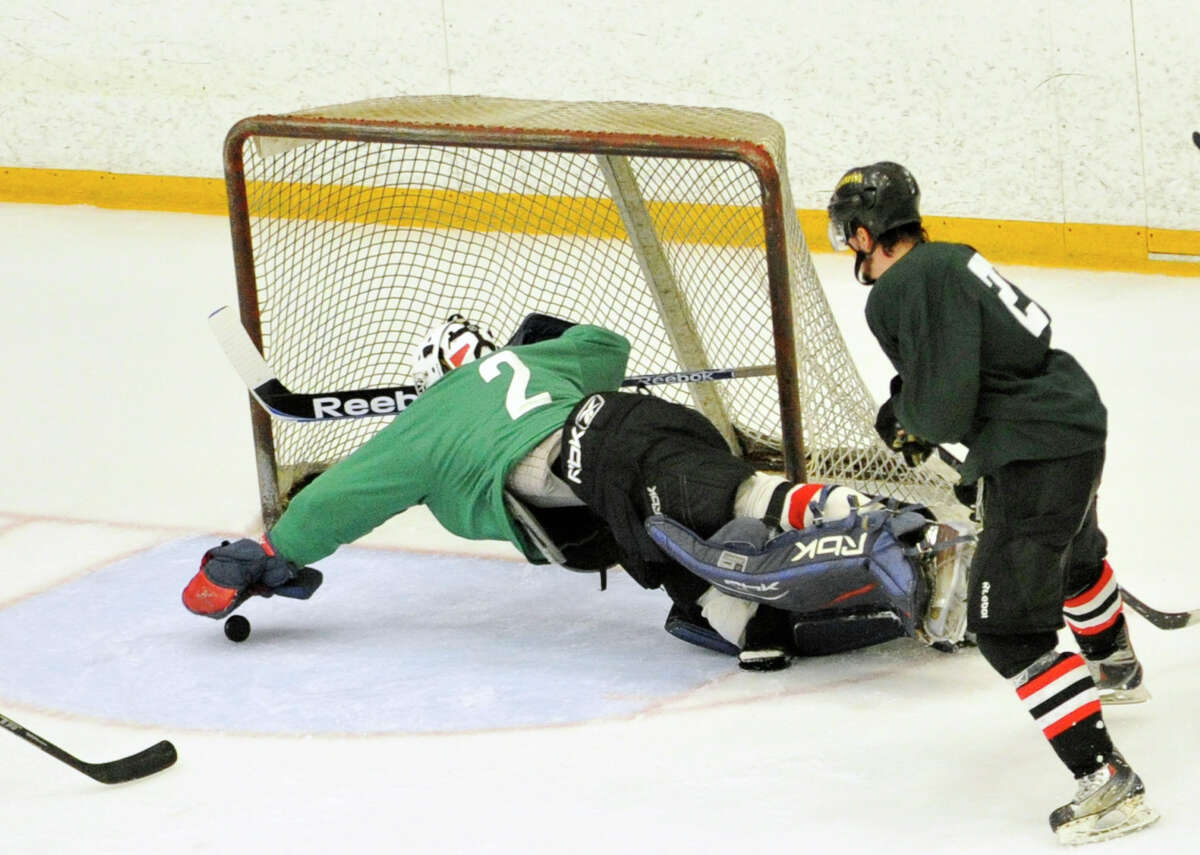 Goalie Travis Hall dives for the puck during the Danbury Whalers' annual Green and White Game at Danbury Ice Arena on Saturday, Sept. 8, 2012.