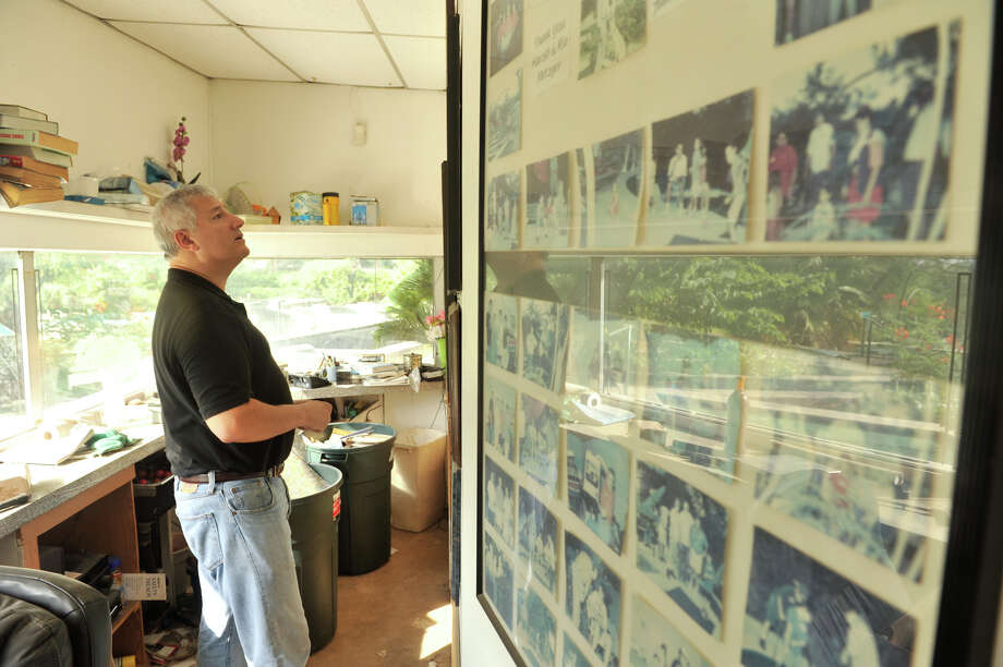 Dr. James Andry looks at old photos on the walls of the Cool Crest office on Aug. 25, 2012. Andry has restored the miniature golf course, which has been closed for several years, to its former glory. Photo: Robin Jerstad,  For The Express-News