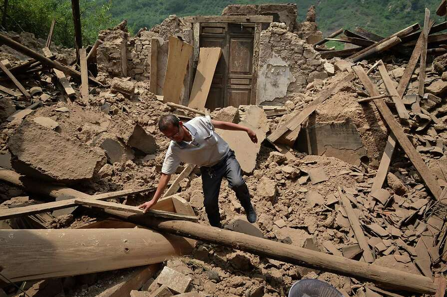 A man checks a destroyed house following an earthquake which hit Luozehe town in Yiliang county in s