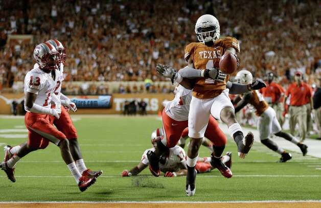 Texas' Mike Davis (1) is pulled down by New Mexico's Joseph Harris (44) as he scores a touchdown during the second quarter of an NCAA college football game on Saturday, Sept. 8, 2012, in Austin, Texas. (AP Photo/Eric Gay) Photo: Eric Gay, Associated Press / AP