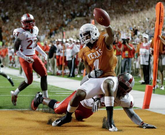 Texas' Mike Davis (1) is pulled down by New Mexico's Joseph Harris (44) while scoring a touchdown during the second quarter of an NCAA college football game on Saturday, Sept. 8, 2012, in Austin, Texas. (AP Photo/Eric Gay) Photo: Eric Gay, Associated Press / AP