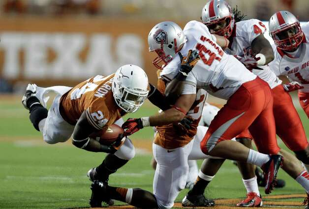 Texas' Joe Bergeron, left, dives past New Mexico defender Dallas Bollema during the second quarter of an NCAA college football game on Saturday, Sept. 8, 2012, in Austin, Texas. (AP Photo/Eric Gay) Photo: Eric Gay, Associated Press / AP