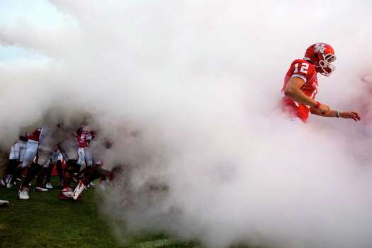 Houston quarterback Rex Dausin (12) runs through a cloud of smoke as he runs out with the team before the start of an NCAA football game against Louisiana Tech at Robertson Stadium, Saturday, Sept. 8, 2012, in Houston. Photo: Brett Coomer, Houston Chronicle / © 2012  Houston Chronicle