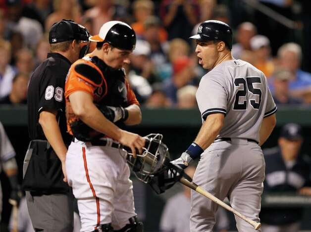 BALTIMORE, MD - SEPTEMBER 08: Catcher Taylor Teagarden #31 of the Baltimore Orioles looks on as Mark Teixeira #25 of the New York Yankees exchanges words with home plate umpire Cory Blaser after being called out looking during the eighth inning at Oriole Park at Camden Yards on September 8, 2012 in Baltimore, Maryland.  (Photo by Rob Carr/Getty Images) Photo: Rob Carr