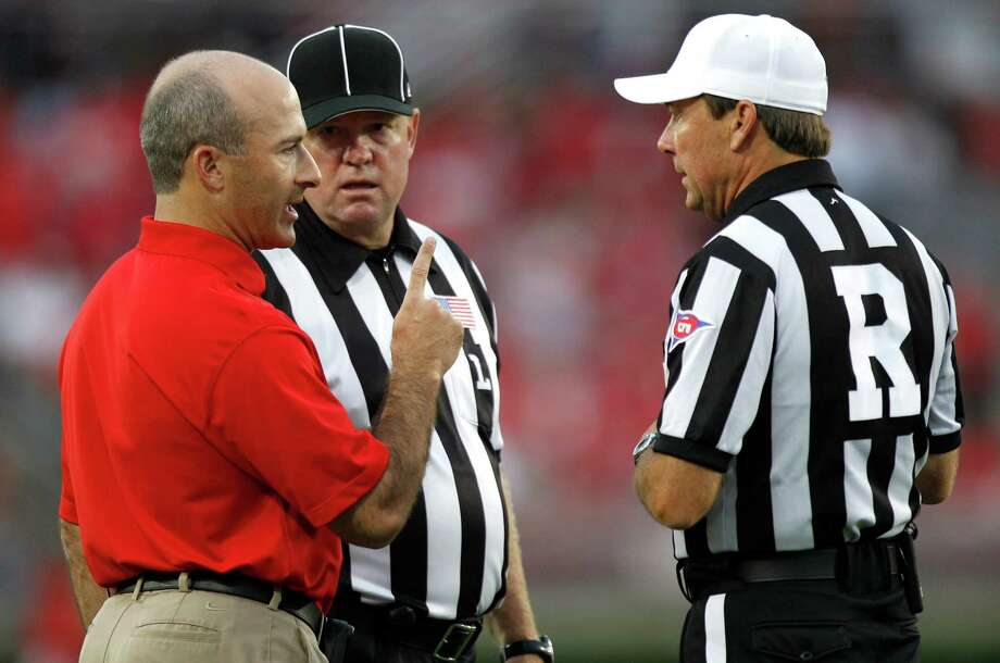 Houston head coach Tony Levine, left, talks to referee James Farmer, right, and line judge Joe Cronin during the first quarter in an NCAA football game against Louisiana Tech at Robertson Stadium, Saturday, Sept. 8, 2012, in Houston. Photo: Brett Coomer, Houston Chronicle / © 2012  Houston Chronicle