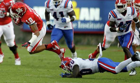 Houston wide receiver Mark Roberts (18) is tripped up by Louisiana Tech defensive back Jamel Johnson (20) during the first quarter in an NCAA football game at Robertson Stadium, Saturday, Sept. 8, 2012, in Houston. Photo: Brett Coomer, Houston Chronicle / © 2012  Houston Chronicle
